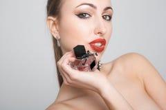 Portret van een mooie sexy dame met parfum, grijze achtergrond Royalty-vrije Stock Afbeelding