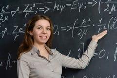 Portret van een mooie student die wiskunde op een bord doen royalty-vrije stock foto