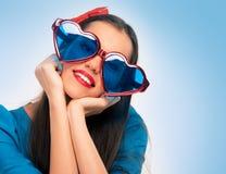 Portret van een mooie vrouw in blauw met hart gevormde glazen Stock Foto's