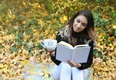 Portret van een mooie vrouw die een boek in een park met een glimlach leest stock fotografie