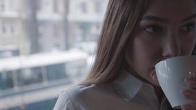 Portret van een mooie vrouw die en in de venster het drinken koffie dicht omhoog denken kijken Mooie vrouw die heet van haar geni stock videobeelden