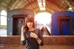 Portret van een mooie vrouw die zich bij het station dichtbij de trein bevinden royalty-vrije stock afbeelding