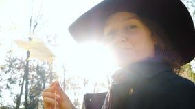 Portret van een mooie vrouw in een hoed Het meisje roteert een geel esdoornblad in haar handclose-up stock video