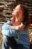Portret van een mooie vrouw met rode die haarzitting op het gras met ogen van achter de zon worden gesloten stock fotografie