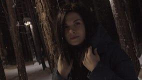 Portret van een mooie vrouw een nachtbos in een sneeuwval stock footage