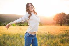 Portret van een mooie vrouw op een gebied bij de zonsondergang Stock Afbeelding
