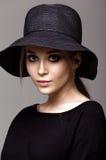 Portret van een mooie vrouw in zwarte hoed Stock Foto
