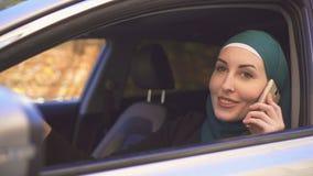 Portret van een mooie vrouwenbestuurder in hijab met een telefoon in de auto royalty-vrije stock afbeelding