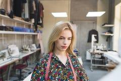 Portret van een ontwerper van kleren op het werk op de achtergrond van een studio Leuke jonge meisjesontwerper van modieuze klere stock foto