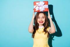 Portret van een opgewekt meisje die in kleding huidige doos houden Royalty-vrije Stock Afbeelding