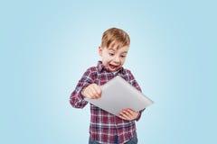 Portret van een opgewekte het glimlachen jongen het spelen tabletcomputer app royalty-vrije stock foto's