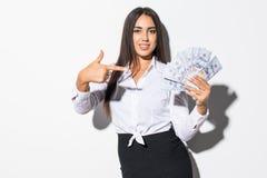 Portret van een opgewekte tevreden die geld van de meisjesholding bankbiljetten en het richten van vinger over witte achtergrond  stock foto