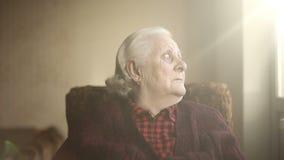 Portret van een oude eenzame mens die uit het venster kijkt stock video
