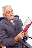 Portret van een oude mens die een boekzitting in zijn leunstoel lezen Stock Fotografie