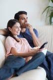 Portret van een paar dat op TV let terwijl het eten van popcorn Stock Foto's
