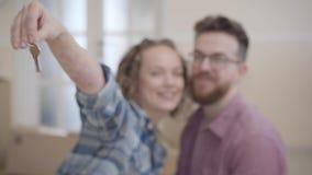 Portret van een paar in liefde, kochten zich zij enkel een huis en het bewegen De vrouw breidt een hand met sleutels tot de camer stock videobeelden