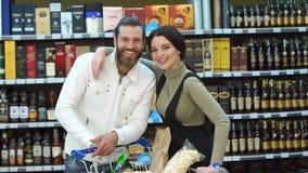 Portret van een paar in een wijnwinkel met een volledige kar van producten stock footage