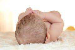 Portret van een pasgeboren baby die op bed met achterhoofd liggen Royalty-vrije Stock Foto's