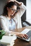 Portret van een peinzende rijpe bedrijfsvrouw die op laptop typen stock afbeeldingen