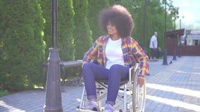 Portret van een positief die jonge Afrikaanse Amerikaanse vrouw gehandicapt in een rolstoel op de straat glimlachen stock footage