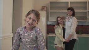 Portret van een pret glimlachend meisje op de achtergrond van twee die oudere zusters omhelzen Familieverhoudingen stock footage