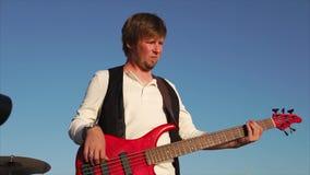 Portret van een professionele musicus die muziek, misschien rots, op basgitaar speelt stock video
