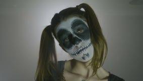 Portret van een psychohalloween-meisje die poppenkostuum dragen die haar schedelhoofd schudden die haar ogen sluiten langzaam en  stock video