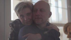 Portret van een rijp paar die terwijl thuis het zitten op de vloer omhelzen Een kale mens met een grijze baard en het houden van stock video