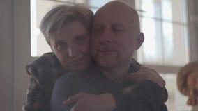 Portret van een rijp paar die terwijl thuis het zitten op de vloer omhelzen Een kale mens met een grijze baard en het houden van stock footage