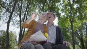 Portret van een rijp paar in liefdezitting op een bank in het park Aanbiddelijke vrouw en oude man samen offerte stock videobeelden