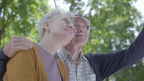Portret van een rijp paar in liefdezitting op een bank in het park Aanbiddelijke vrouw en oude man samen offerte stock video