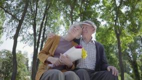 Portret van een rijp paar in liefdezitting op een bank in het park De volwassen vrouw houdt een mooi boeket van bloemen stock video