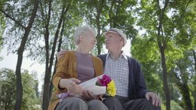 Portret van een rijp paar in liefdezitting op een bank in het park De volwassen vrouw houdt een mooi boeket van bloemen stock footage