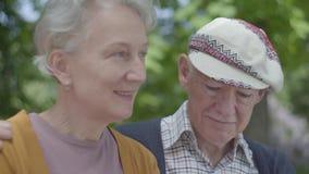 Portret van een rijp paar in liefdezitting op een bank in het park Volwassen vrouw en bejaarde echtgenoot Tedere verhouding stock video