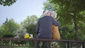 Portret van een rijp paar in liefdezitting op een bank in het park Volwassen vrouw en oude man samen offerte stock footage