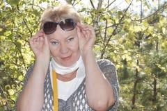 Portret van een rijpe vrouw met zonnebril op zijn voorhoofd Stock Foto