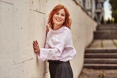 Portret van een roodharige lachende vrouw die op middelbare leeftijd zich dichtbij een muur van steentegels bevinden Bewolkte de  stock fotografie