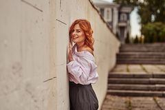 Portret van een roodharige lachende vrouw die op middelbare leeftijd zich dichtbij een muur van steentegels bevinden Bewolkte de  stock afbeeldingen