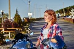 Portret van een roodharige vrouw op middelbare leeftijd na een motorfietsrit op een zonnige avond in de avond royalty-vrije stock afbeelding