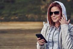 Portret van een roodharige vrouw op middelbare leeftijd in zonnebril en een regenjas die een smartphone bekijken Zonnige de lente stock afbeelding
