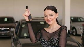 Portret van een schitterend meisje met sleutels tot een nieuwe auto in de toonzaal stock videobeelden