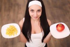 Portret van een schitterende jonge donkerbruine vrouw die de keuzen van het dieetvoedsel tonen Royalty-vrije Stock Afbeeldingen