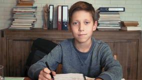 Portret van een schooljongen bij zijn bureau stock footage