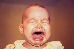 Portret van een schreeuwende baby Scheuren op het gezicht royalty-vrije stock fotografie