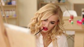 Portret van een sexy meisjeskunstenaar met penselen in hand voor het canvas stock video