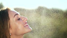 Portret van een sexy, mooi jong blondemeisje, onder een lichte de zomerregen, in de zonstralen, op een groene weide Het meisje stock footage