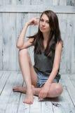 Portret van een slank aantrekkelijk meisje op de houten vloer Stock Afbeelding