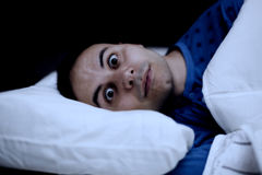 Portret van een slapeloosheidsmens in zijn bed Stock Foto