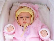 Portret van een slaperig drie-maand-oud babymeisje die in een wieg in roze kleren liggen stock foto's