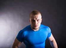 Portret van een spier agressieve jonge mens die zich in studio op zwarte studioachtergrond bevinden Mening met exemplaarruimte Stock Foto's